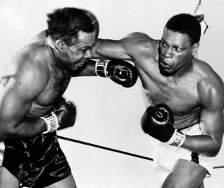 Nino Valdes, right, of Cuba, jolts the veteran Archie Moore with an overhand right to the head in the third round of their scheduled 15-round heavyweight fight at Cashman Field May 2, 1955.