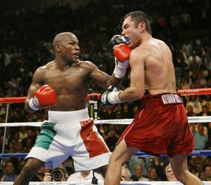 Floyd Mayweather Jr., left, lands a left on Oscar De La Hoya during the twelfth round of their WBC super welterweight world championship boxing match on Saturday, May 5, 2007, at the MGM Grand Garden Arena  in Las Vegas. (AP Photo/Kevork Djansezian)