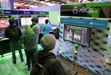 People look over an Xbox on Windows display in the Microsoft booth at the Game Developers Conference, Wednesday, March 4, 2015, in San Francisco.