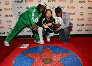 DJ Steve Aoki, flanked by Flavor Flav and Coolio, receives a celebrity star at Brenden Theaters in the Palms on Friday, March 6, 2015, in Las Vegas.