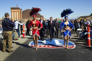 Showgirls Cece Correia, left, and Tala Marie lead a procession of government officials, including Governor Brian Sandoval, center, during a groundbreaking ceremony for the Interstate-11/Boulder City Bypass project near Boulder City Monday, April 6, 2015. The $318 million project is expected to be completed in 2018 and create about 4,000 jobs.