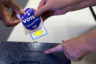 A voter deposits her voting card into a ballot box during voting at Becker Middle School in Summerlin Tuesday, April 7, 2015.