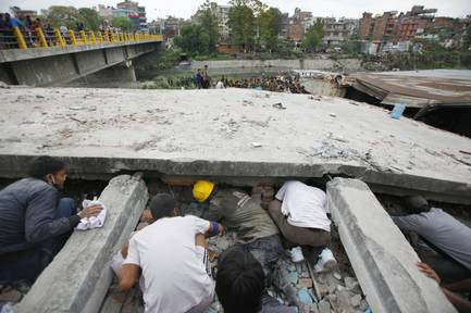 Rescuers look for victims under a building that collapsed after an earthquake in Kathmandu, Nepal, on Saturday, April 25, 2015. A magnitude-7.8 earthquake shook Nepal's capital and the densely populated Kathmandu Valley, causing extensive damage with toppled walls and collapsed buildings, officials said.
