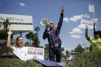Michelle Balistreri and Chandler Gray attend a rally in front of NV Energy on Wednesday, April 22, 2015, in Las Vegas. Hundreds of activists gathered outside NV Energy headquarters in Las Vegas to protest a state cap affecting rooftop solar installations and urge the Legislature to lift it.