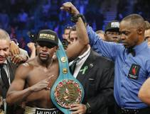 Floyd Mayweather Jr., celebrates his victory over Manny Pacquiao with the champion's belt after their welterweight title fight on Saturday, May 2, 2015, in Las ...