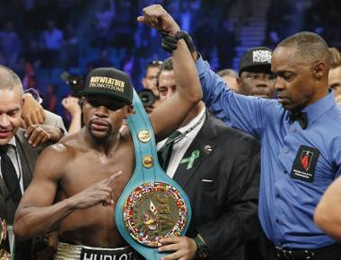Floyd Mayweather Jr., celebrates his victory over Manny Pacquiao with the champion's belt after their welterweight title fight on Saturday, May 2, 2015, in Las Vegas. At right is referee Kenny Bayless.
