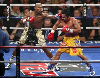 Floyd Mayweather Jr. connects to the chin of Manny Pacquiao late in their fight Saturday, May 2, 2015, at MGM Grand Garden Arena.