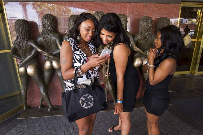 Crystal Mebame, left, Krissy Lee, center, and Brittany Perkins of Baltimore look at a photo on a phone after posing by the Crazy Girls sculpture in from of the Riviiera Monday, May 4, 2015. The Riviera closes it's doors at noon.