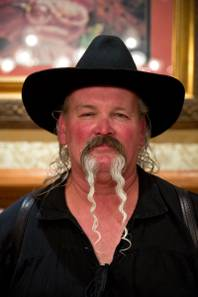 James Watson poses for a portrait after winning Longest Mustache at the Whiskerino Contest, a facial hair competition during the Las Vegas Elk's Helldorado Days, Sat May 16, 2015.