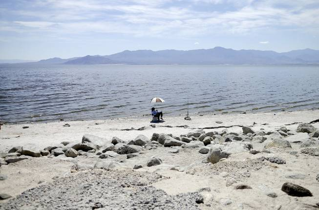 In this April 30, 2015, photo, Ed Victoria of Los Angeles sits under an umbrella as he fishes for tilapia along the receding banks of the Salton Sea near Bombay Beach, Calif. The lake is shrinking and on the verge of getting smaller as more water goes to coastal cities.