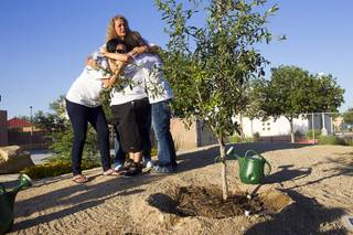 Family and friends of Joseph Wilcox embrace by a tree planted in memory of Wilcox in Walnut Park, adjacent to Metro Police Northeast Area Command, Monday, June 8, 2015. Wilcox was killed on June 8, 2014 while trying to stop two armed assailants that ambushed and killed Metro Police Officers Alyn Beck and Igor Soldo.