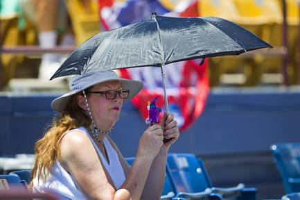 Las Vegas 51s fan Aoife (no last name provided) tries to stay cool with an umbrella and portable fan as she watches the 51s take on the Reno Aces on Sunday, June 14, 2015, at Cashman Field. Warm weather is expected in the triple digits this week with an average high temperature of 108 degrees.