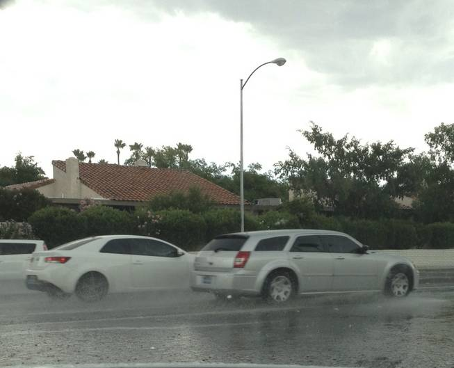 Motorists drive through puddles of rain on Eastern Avenue at Mohigan Way after a thunderstorm swept through the central Las Vegas Valley on Sunday, June 14, 2015.