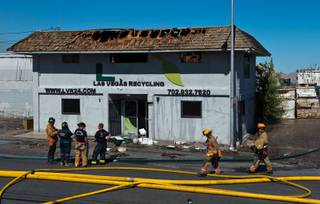 Firefighters gather outside of the Las Vegas Recycling building which was severely damaged by fire on Tuesday, June 16, 2015.