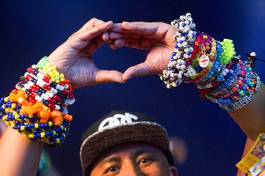 A man forms a heart with his hands during the final night of the Electric Daisy Carnival (EDC) at the Las Vegas Motor Speedway Sunday, June 21, 2015.