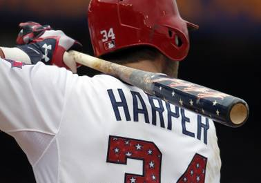 Washington Nationals right fielder Bryce Harper bats with a patriotic-themed bat with stars, stripes and a Washington skyline.