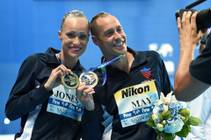 "New world champions Christina Jones and Bill May, of Cirque du Soleil's ""O"" at Bellagio, with their gold medals for mixed synchronized swimming at the 2015 FINA World Championships on Sunday, July 26, 2015, in Kazan Russia."