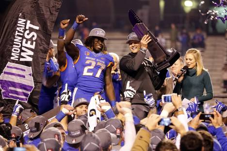 Boise State running back Jay Ajayi (27) cheers while head coach Bryan Harsin hoists the Mountain West Conference championship trophy after beating Fresno State on Saturday, Dec. 6, 2014, in Boise, Idaho.