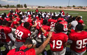 UNLV players, coaches and staff take a moment for prayer following a scrimmage at Nellis AFB on Saturday, August 15, 2015.