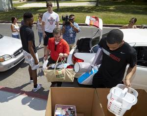 UNLV President Len Jessup and members of the UNLV men's basketball team help unload cars during freshman dorm move-in day at Dayton Hall on Wednesday, Aug. 19, 2015.