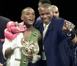 Floyd Mayweather, left, of Grand Rapids, Mich., stands in the ring with his father, Floyd Mayweather Sr., after defeating Diego Corrales of Sacramento, Calif., in their WBC super featherweight championship fight in Las Vegas, in this Jan. 20, 2001 file photo.