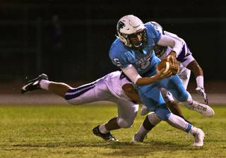 Foothill quarterback Devon Mueller, 5, escapes a sack and turns it into positive yards in a game against Silverado on Friday, Sept. 4, 2015.