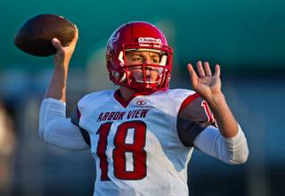 Arbor View QB Hayden Bollinger, 18, readies to fire a pass in the fading light as his team warms up to face Green Valley during high school football on Friday, September 11, 2015.