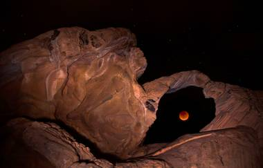 A supermoon and total lunar eclipse break through clouds Sunday, Sept. 27, 2015, over Valley of Fire State Park.
