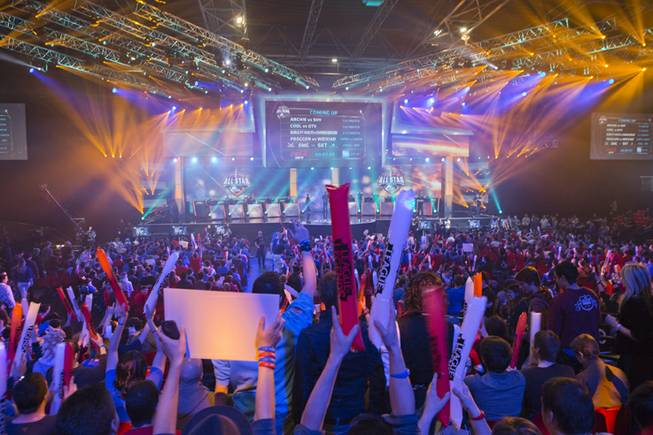 "In this May 11, 2014, photo, fans watch the opening ceremony of the ""League of Legends"" season four World Championship Final between South Korea and China's Royal Club in Paris. Around the world, fans gather en masse to watch video game players compete in high-stakes tournaments. Fans also bet on the outcomes."