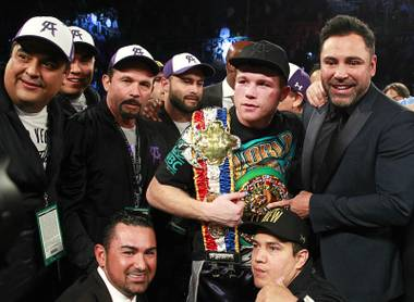 Canelo Alvarez of Mexico poses with Oscar De La Hoya, right, and members of his camp after beating Miguel Cotto of Puerto Rico at the Mandalay Bay Events Center Saturday, Nov. 21, 2015. Alvarez beat Cotto to win the WBC middleweight title.
