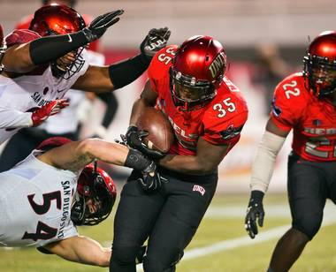 UNLV's Xzaviar Campbell (35) runs past San Diego State'sCalvin Munson (54) and others in an attempt to keep a drive going during their game at Sam Boyd Stadium on Friday, November 21, 2015.