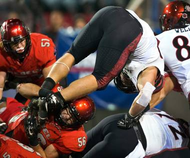 UNLV's Ryan McAleenan (56) does his best to hold back  San Diego State's Dakota Gordon (46) who dives towards the end zone during their game at Sam Boyd Stadium on Friday, November 21, 2015.