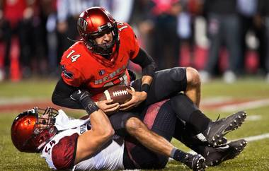 UNLV QB Kurt Panandech (14) is thrown for a loss by San Diego State's Calvin Munson (54) during their game at Sam Boyd Stadium on Friday, November 21, 2015.