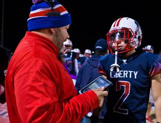 Liberty High School head coach Richard Muraco utilizes hand-held technology on the sidelines while consulting with Ethan Dedeaux (2) to give an edge to his football players and coaches while facing Green Valley in their high school state quarterfinal game at Liberty on Friday, November 20, 2015.