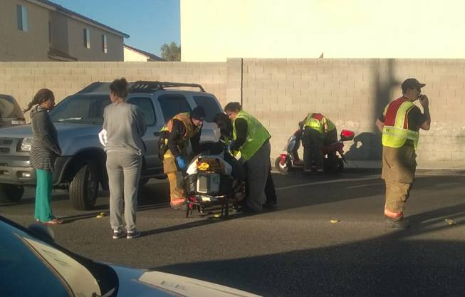 A person is seen on a stretcher after a collision between a motor scooter and a vehicle on Monday, Nov. 30, 2015, at the intersection of South Duneville Street and West Reno Avenue, near Jydstrup Elementary School.