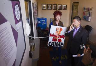 Nevada State Sen. Mark Manendo, right, and Stacia Newman, president of Nevada Political Action For Animals, try to get Boulder City Police Chief Bill Conger on the phone during a protest at the Boulder City Police Department in Boulder City Thursday, Dec. 3, 2015. Protesters want charges to be brought against the city's former animal shelter supervisor for killing too many animals.