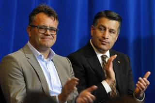 Dag Reckhorn, left, global vice president of manufacturing for Faraday Future, and Nevada Governor Brian Sandoval applaud during a news conference at the Sawyer State Building in Las Vegas Thursday, Dec. 10, 2015. Reckhorn and the governor discussed plans for the Faraday Future electric-car factory in the city of North Las Vegas.