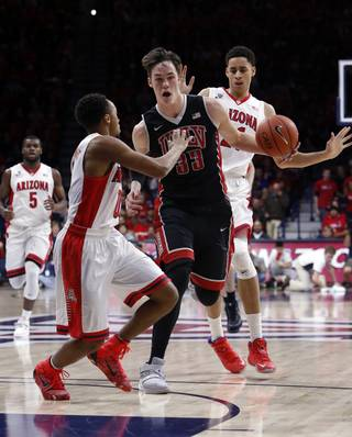 UNLV forward Stephen Zimmerman Jr. (33) drives on Arizona guard Parker Jackson-Cartwright during the first half of an NCAA college basketball game Saturday, Dec. 19, 2015, in Tucson, Ariz. (AP Photo/Rick Scuteri)