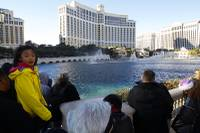 Tourists watch a fountain show at Bellagio on Christmas Day on Friday, Dec. 25, 2015.