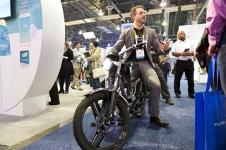 Josh Rasmussen, of Bolt Mortorbikes, cruises around the showroom floor of CES 2016 on an M-1 Electric/Hybrid motorbike, Wed. Jan 6, 2016.