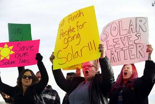 Tera Mills, center, and other solar supporters rally in front of Public Utilities Commission offices Wednesday, Jan 13, 2016. Mills said her parents have installed solar panels on their rooftop.
