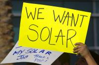 Solar supporters hold signs during a rally in front of Public Utilities Commission offices Wednesday, Jan 13, 2016.