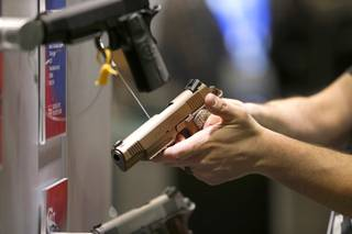 A man looks over a Colt handgun during the SHOT (Shooting, Hunting and Outdoor Trade) Show at the Sands Expo Tuesday, Jan. 19, 2016.
