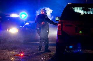 A Oregon State police officer stands by a vehicle as police officers block Highway 395 in Seneca, Ore., Tuesday, Jan. 26, 2016. Authorities said shots were fired Tuesday during the arrest of members of an armed group that has occupied a national wildlife refuge in Oregon for more than three weeks. (Dave Killen/The Oregonian via AP)