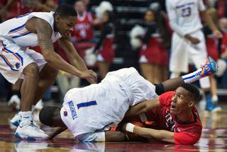 Boise State guard Mikey Thompson (1) rolls over UNLV guard Patrick McCaw (22) fighting for a loose ball during their game at the Thomas & Mack Center on Wednesday, January 27, 2016.