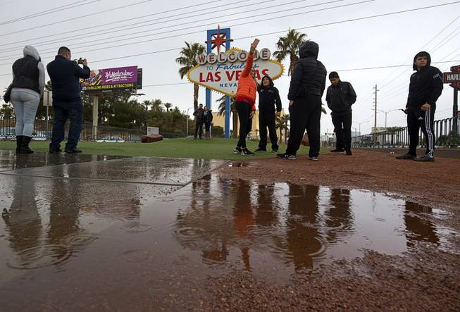 "Tourists brave rainy weather to take photos in front of the ""Welcome to Las Vegas"" sign Sunday, Jan. 31, 2016."
