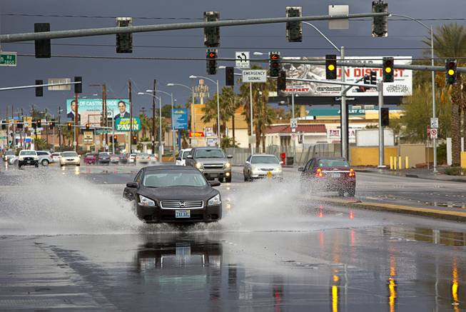 A motorist drives through rain run-off on Valley View Boulevard near Spring Mountain Road on Sunday, Jan. 31, 2016.