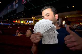 Marc Z (no last name given) of Chicago displays his betting tickets as he watches Super Bowl 50 in the Westgate Super Book Sunday, Feb. 7, 2016.