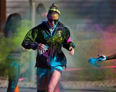 Another runner is dusted with more color as she reaches the finish line of the Las Vegas Color Vibe 5K run at Craig Ranch Park on Saturday, February 6 2016.  A portion of the proceeds from the event will benefit the Nevada Childhood Cancer Foundation.  L.E. Baskow