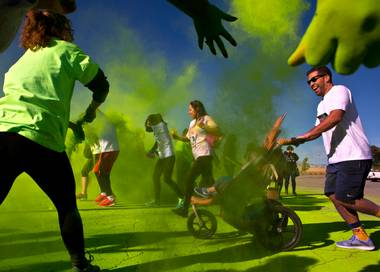 Runners are tossed with green dust as they move past a checkpoint during the Las Vegas Color Vibe 5K run at Craig Ranch Park on Saturday, February 6 2016.  A portion of the proceeds from the event will benefit the Nevada Childhood Cancer Foundation.  L.E. Baskow